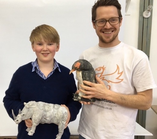 Young artist with his artwork and James, the tutor